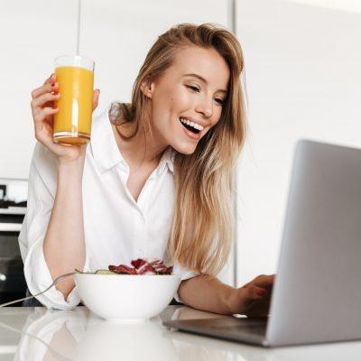 Joyful young woman drinking orange juice